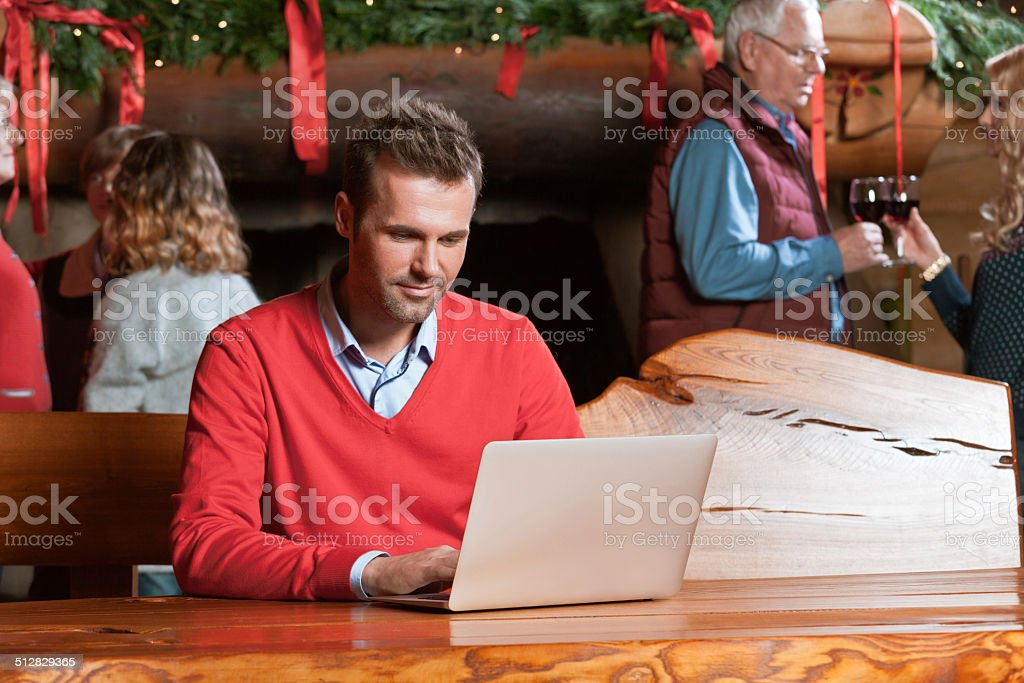 Man using computer during Christmas A man sitting by the table in the mountain house and using laptop with people talking by the fireplace in the background. Active Seniors Stock Photo