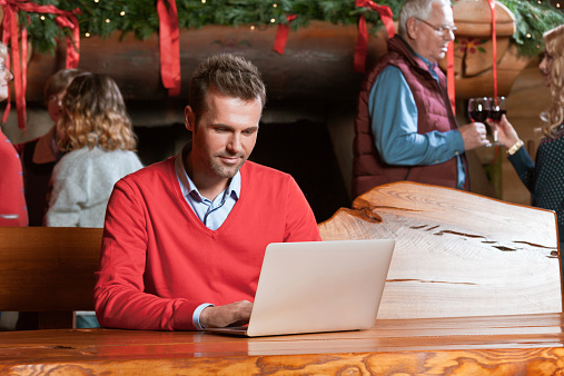 Man Using Computer During Christmas Stock Photo - Download Image Now