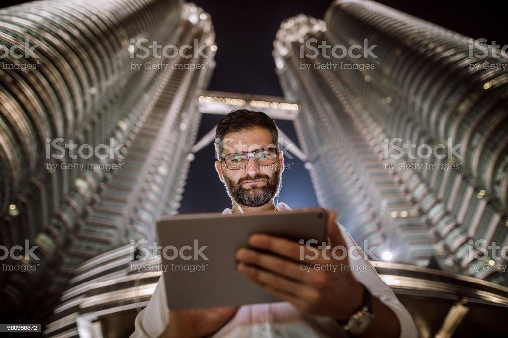Mann mit Computer vor Petronas Towers - Lizenzfrei Abgeschiedenheit Stock-Foto