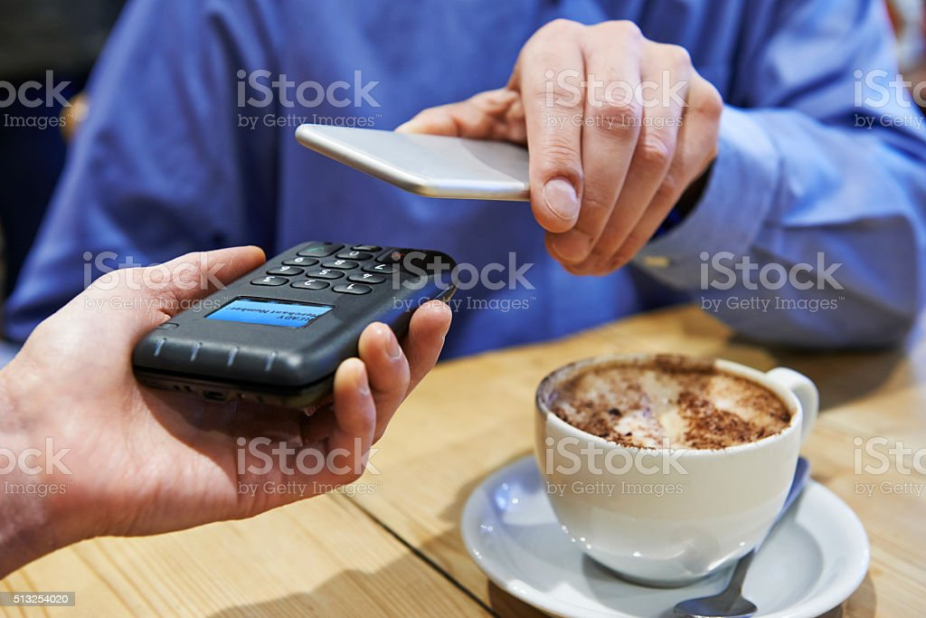 Man Using Contactless Payment App On Mobile Phone In Cafe stock photo