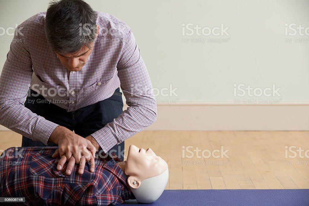 Man Using CPR Technique On Dummy In First Aid Class stock photo