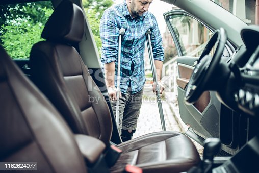 istock man using crutches is about to take the car 1162624077