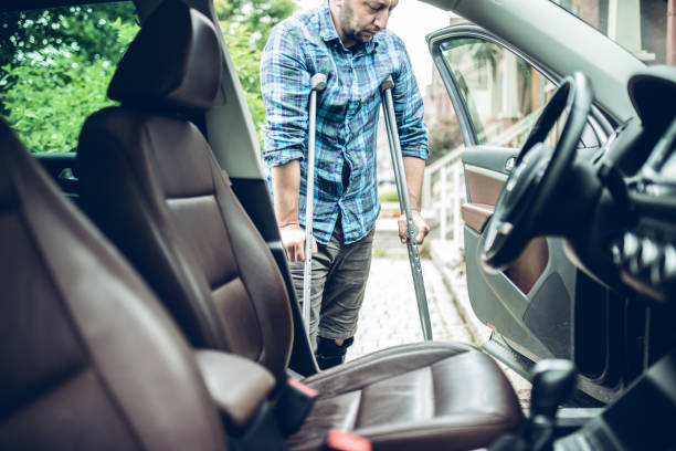 man using crutches is about to take the car stock photo
