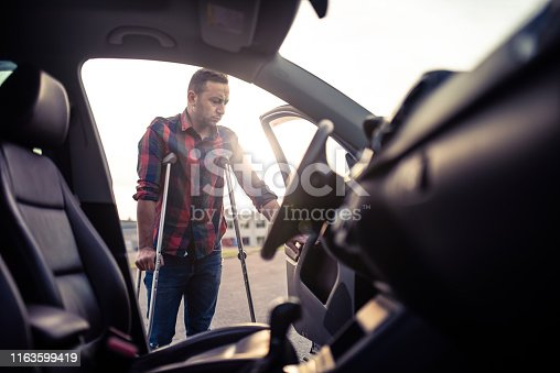 istock Man using crutches is about to take the car 1163599419