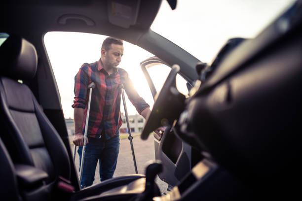 mann mit krücken ist im begriff, das auto zu nehmen - warchi stock-fotos und bilder