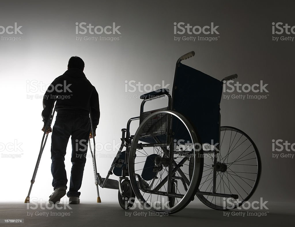 Man using crutches walking away from wheelchair stock photo
