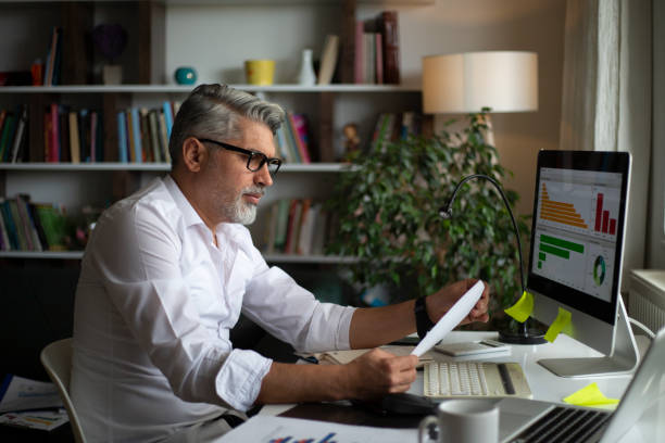 Man using desktop pc at desk in home office stock photo
