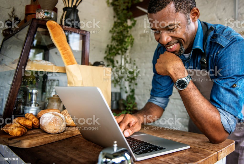 Man using devices for online business order at bakehouse stock photo