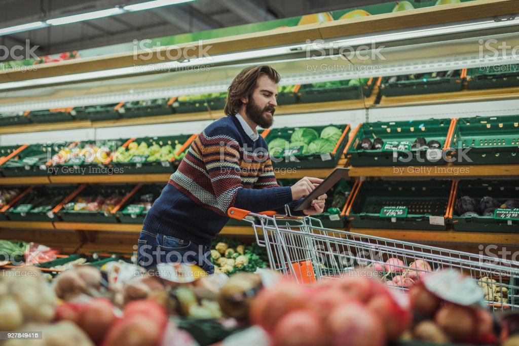 Man using digital tablet and shopping in the market place stock photo