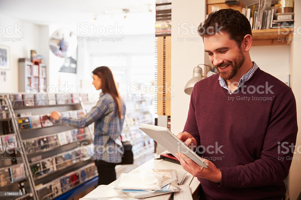 Man using digital tablet behind the counter at record shop stock photo