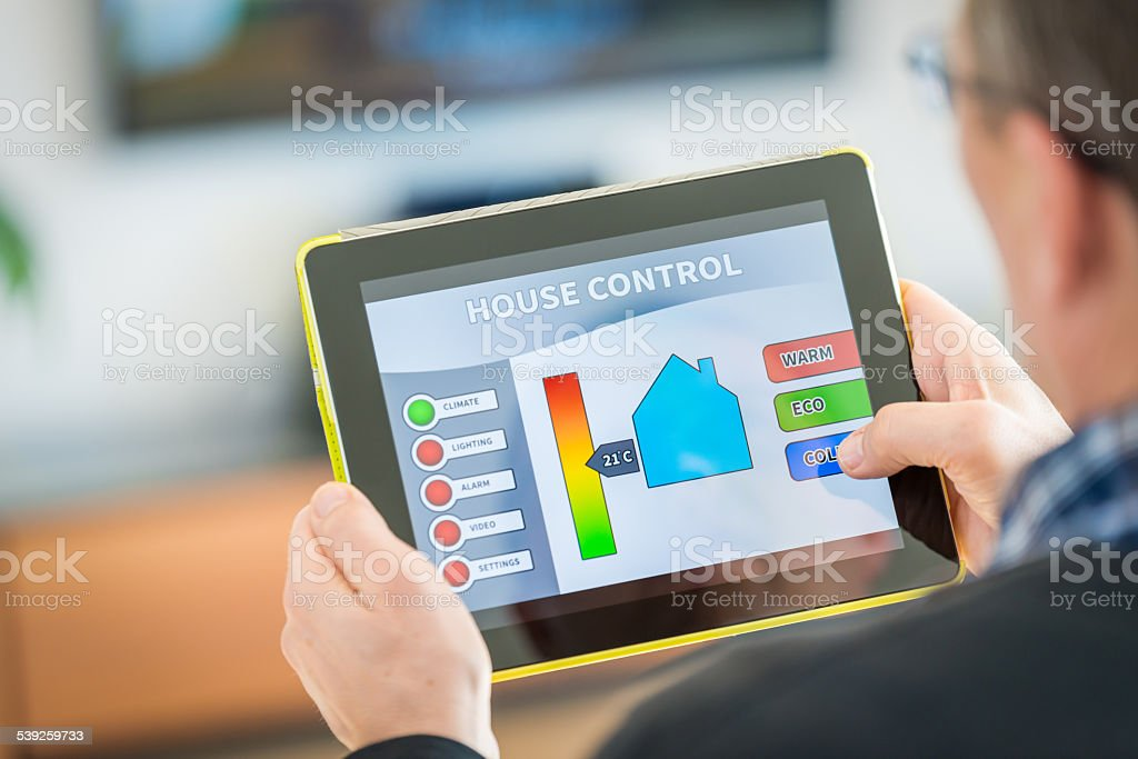 Man using digital tablet for remote house control stock photo