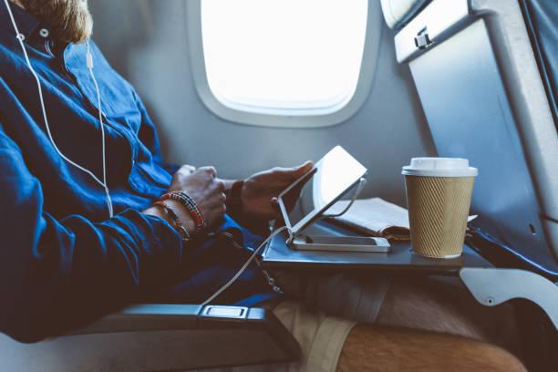 Mann mit digitalem Tablet im Flugzeug – Foto