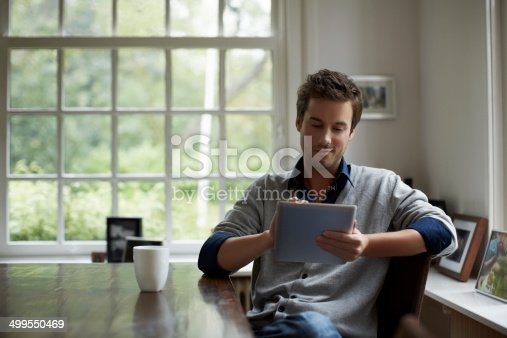 Young man using digital tablet while having coffee at table in cottage