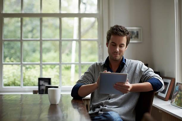 man using digital tablet in cottage - 디지털 태블릿 사용하기 뉴스 사진 이미지