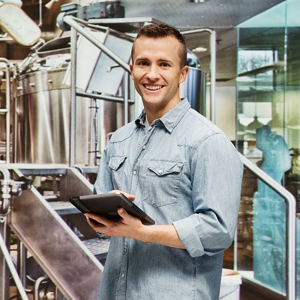 Man using digital tablet in factory stock photo