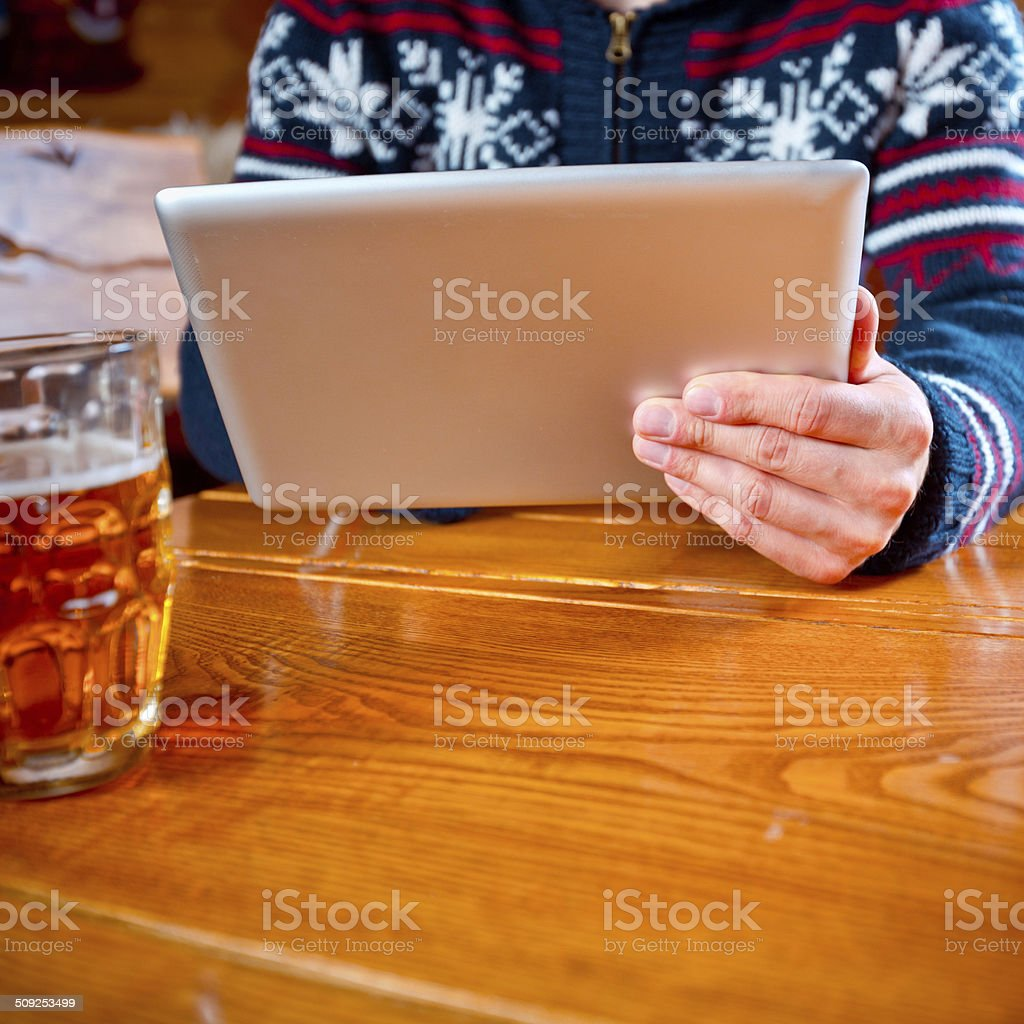 Man using digital tablet Man sitting in a mountain restaurant after skiing, enjoying beer and using a digital tablet. Close up of hand and digita tablet. Adult Stock Photo