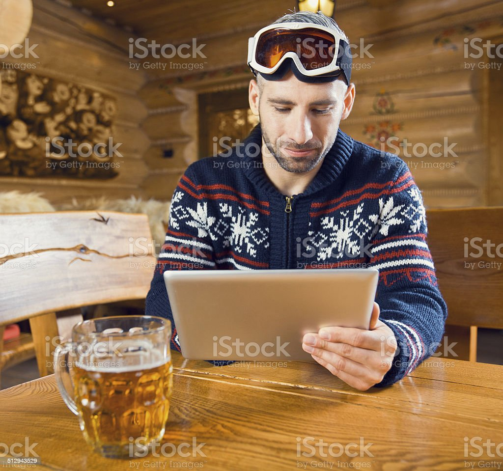 Man using digital tablet Man sitting in a mountain restaurant after skiing, enjoying beer and using a digital tablet.  35-39 Years Stock Photo