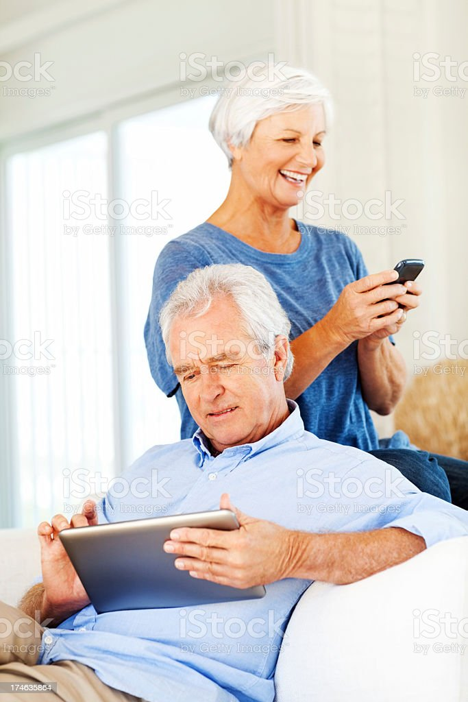 Man Using Digital Tablet While Woman Messaging On Smart Phone royalty-free stock photo