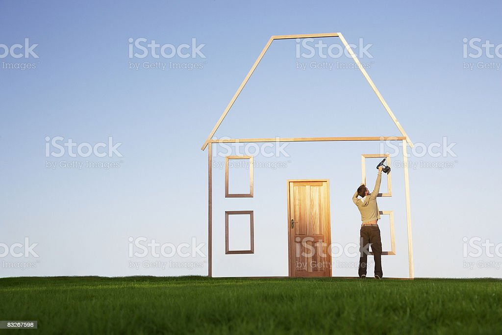Man using drill on house outline stock photo