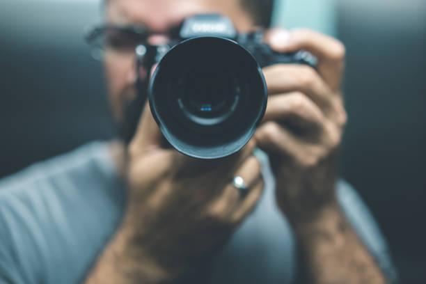 mann mit dslr-kamera - fotografische themen stock-fotos und bilder