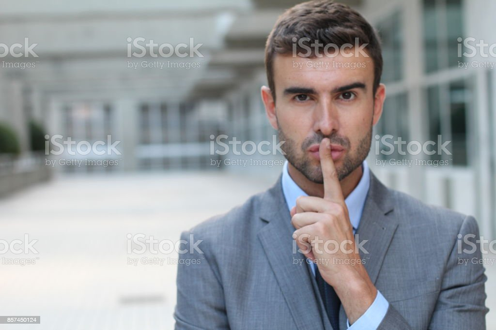 Man using finger sign to command silence stock photo