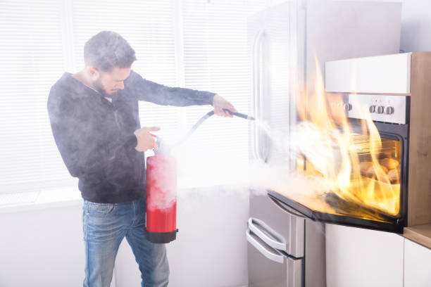 man using fire extinguisher to stop fire coming from oven - burned oven imagens e fotografias de stock