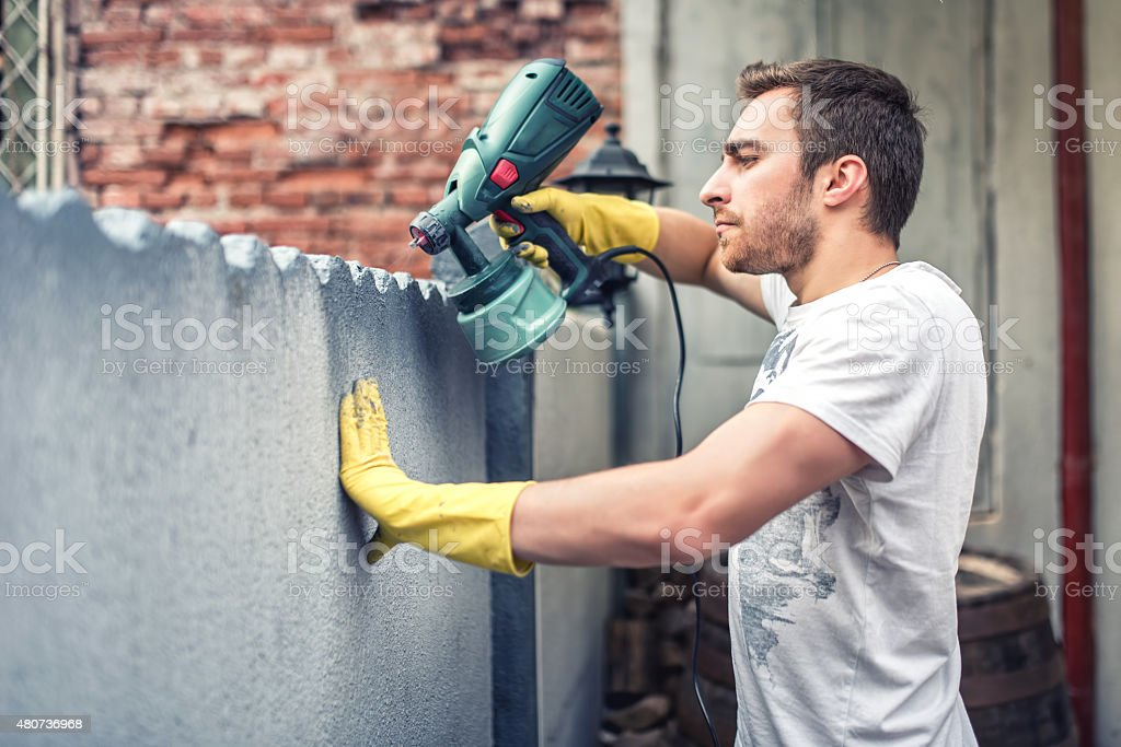 Man using gloves painting grey wall with spray paint gun stock photo