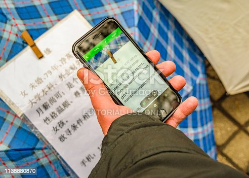 SHANGHAI, CHINA, DECEMBER - 2018 - Man using google translate to read chinese letters at people square, shanghai, china