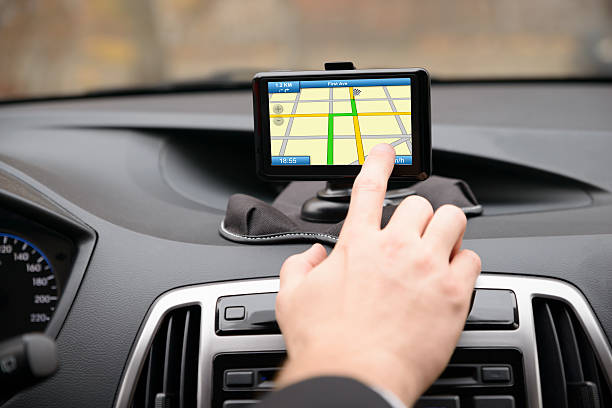 Man Using Gps Navigation While Driving Close-up Of Man Using Gps Navigation System In Car global positioning system stock pictures, royalty-free photos & images