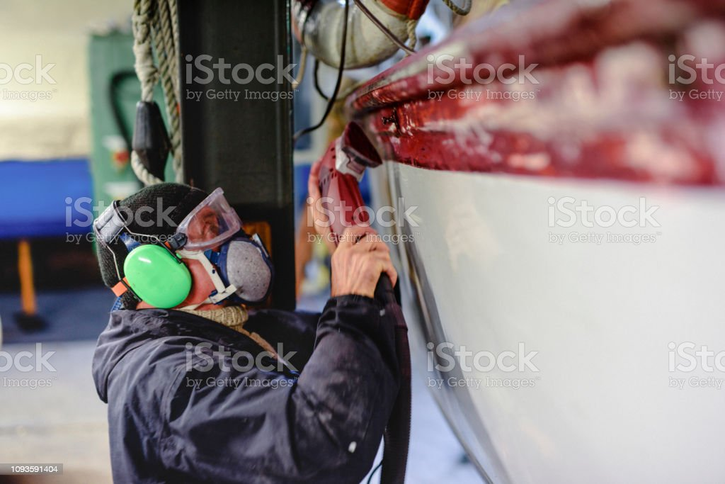 Man using grinding machine, maintenance of sailing yacht in boathouse stock photo