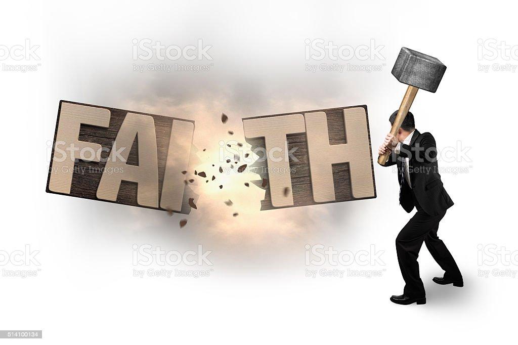 Man using hammer cracking FAITH word wooden board. stock photo