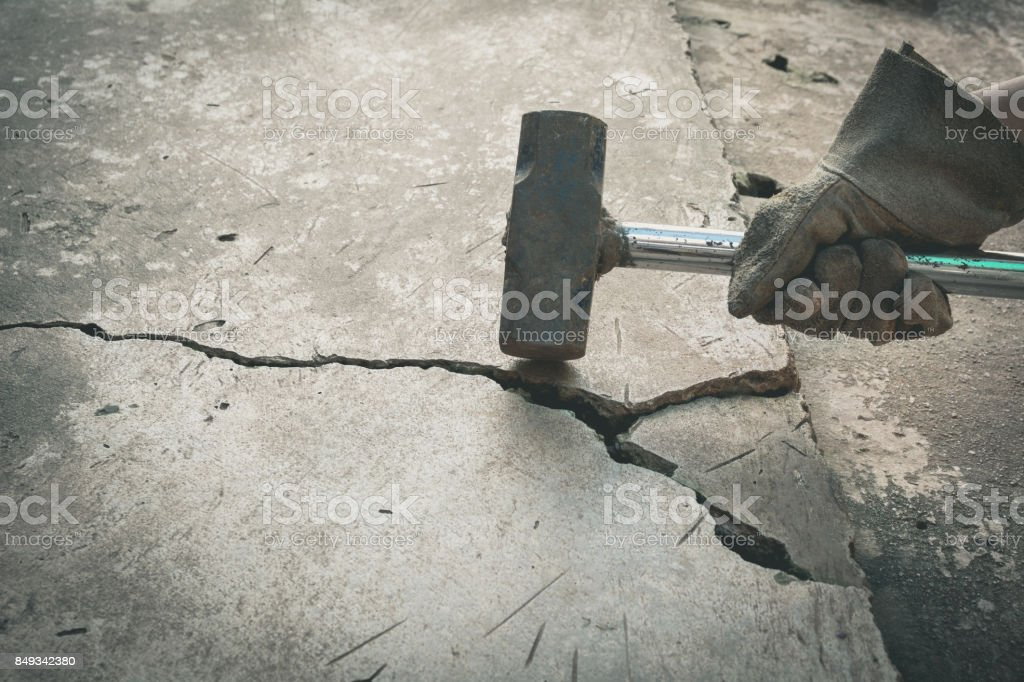 Man using hammers for breaking the broken concrete. Power, strength and destruction concept. stock photo