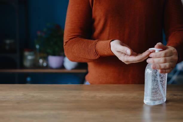 Mann mit Handdesinfektionsmittel, um seine Hände zu reinigen – Foto