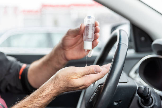 Man using hand sanitizer while sitting in car stock photo