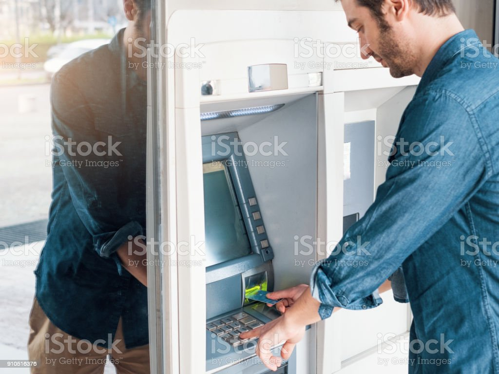 Man using his credit card in an atm for cash withdrawal stock photo