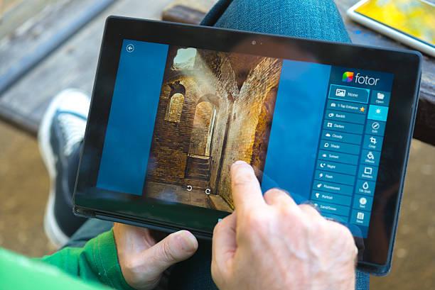 mann mit seinem microsoft surface tablet im park - microsoft windows stock-fotos und bilder