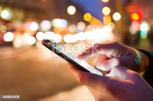 493694506istockphoto Man using his Mobile Phone in the street, bokeh 493694506