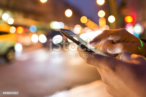 istock Man using his Mobile Phone in the street, bokeh 493694552