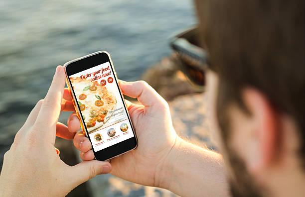 man using his mobile phone  to order pizza online - on demand bildbanksfoton och bilder