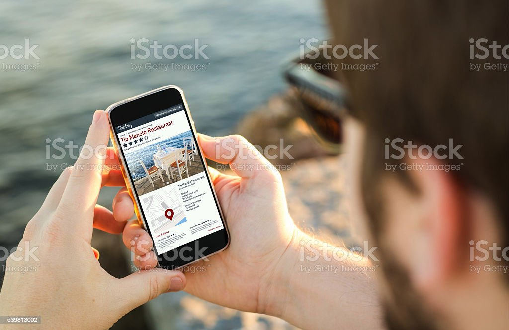 Man using his mobile phone  to search on online dire stock photo