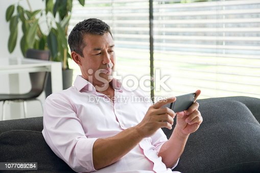 istock Man using his smartphone at home 1077089284