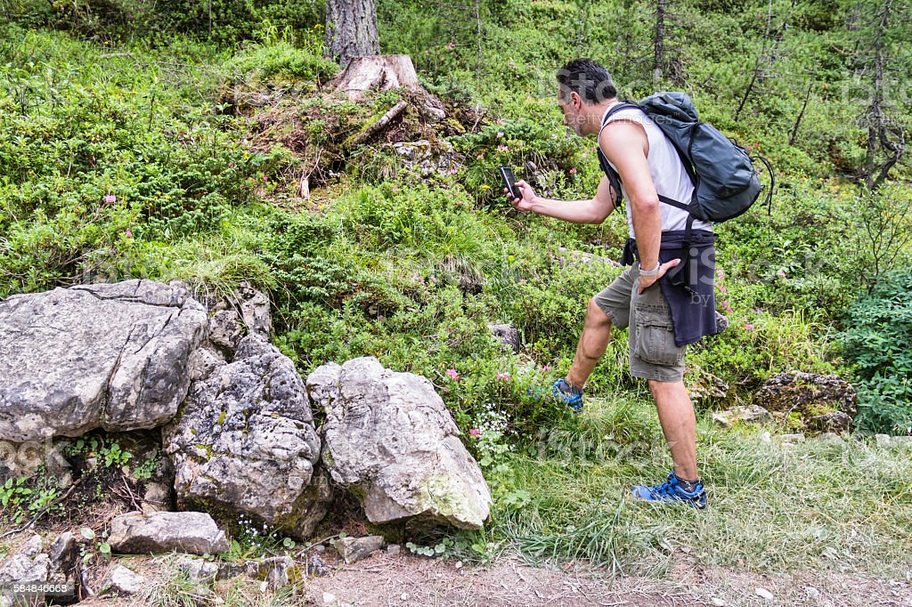 Man using his smartphone during hiking activity (playing or other) stock photo