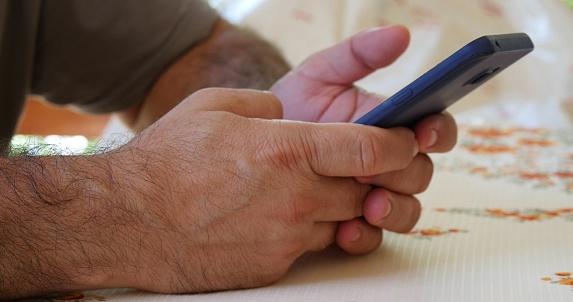 Man using his smartphone with to scrolling and tapping on screen.