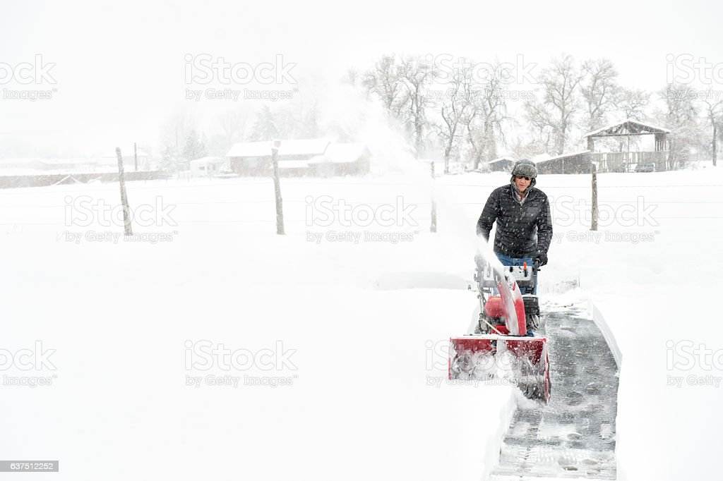 Man Using His Snow Blower To Clear His Driveway stock photo