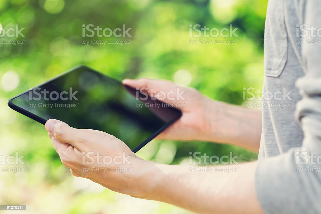 Man using his tablet computer outside stock photo