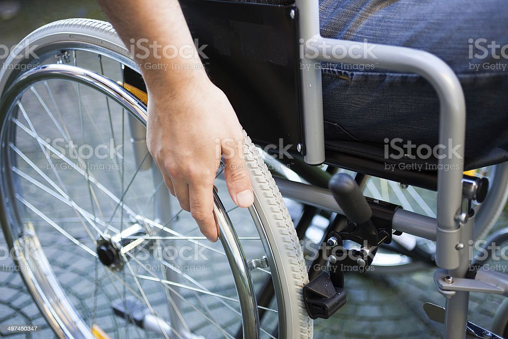 Man using his wheelchair Paralyzed man using his wheelchair Accessibility Stock Photo