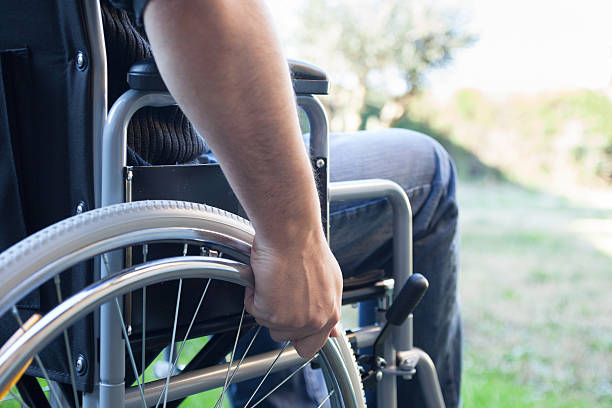 Man using his wheelchair Paralyzed man using his wheelchair paralysis stock pictures, royalty-free photos & images
