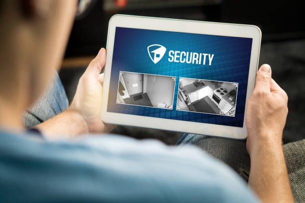 Man using home security system and application in tablet. Watching protection camera live footage inside a house or apartment. stock photo
