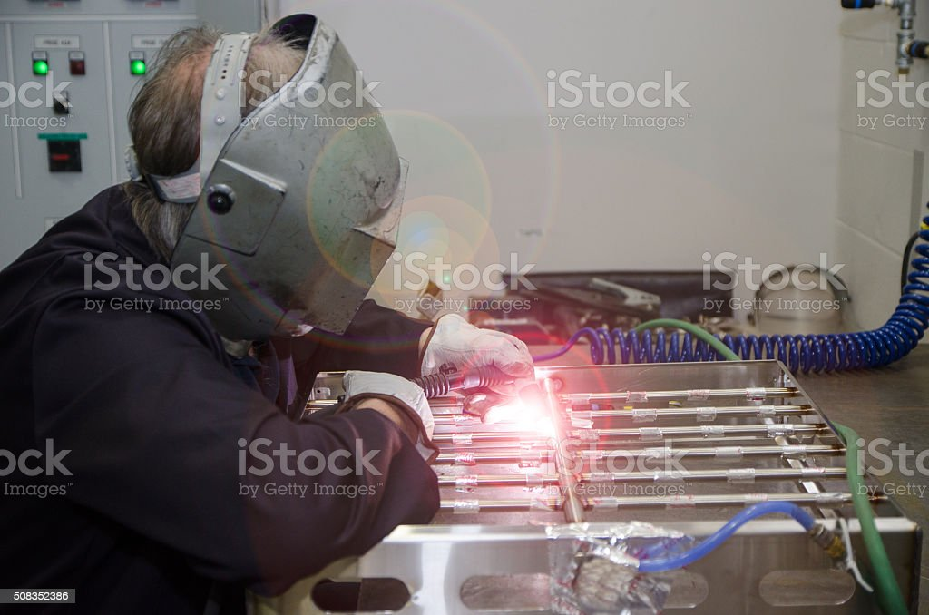 Man using industrial gas welder, wearing a protection helmet and...