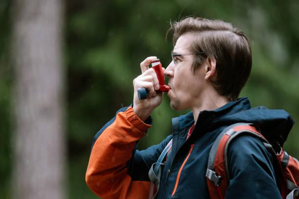 Man Using Inhaler While Hiking Outdoors